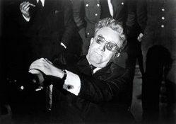 Peter Sellers, as Dr. Strangelove, struggles to control his alien hand.